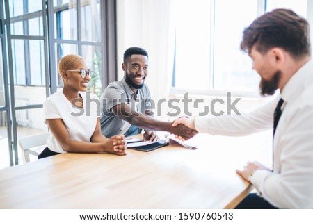 Joyful African American couple shaking hands with unrecognizable bearded realtor in formal clothes while sitting at table in new apartment