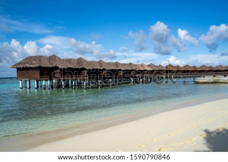 Beautiful over the water bungalow beach villas in the Maldives on the Indian Ocean on a sunny day #1590790846