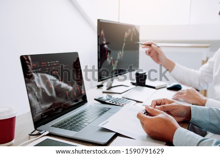 Two business stock brokers stress and looking at monitors displaying financial stock graph report information. #1590791629