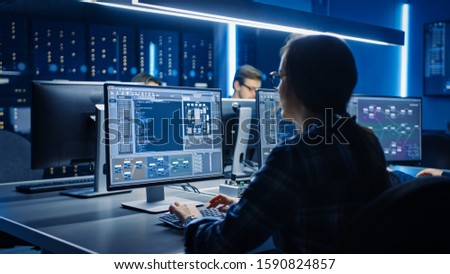 Smart Female IT Programer Working on Desktop Computer in Data Center System Control Room. Team of Young Professionals Doing Code Programming #1590824857