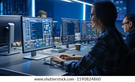 Smart Female IT Programer Working on Desktop Computer in Data Center System Control Room. Team of Young Professionals Doing Code Programming #1590824860