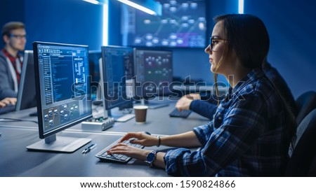 Smart Young Female IT Programer Working on Desktop Green Mock-up Screen Computer in Data Center System Control Room. Team of Young Professionals Programming Sophisticated Code Royalty-Free Stock Photo #1590824866