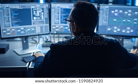 Professional IT Programer Working in Data Center on Desktop Computer with Three Displays, Doing Development of Software and Hardware. Displays Show Blockchain, Data Network Architecture Concept #1590824920
