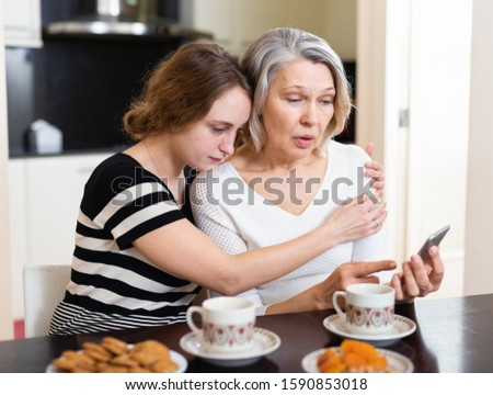 Dissatisfied mother and daughter using mobile gadget at kitchen table at home #1590853018