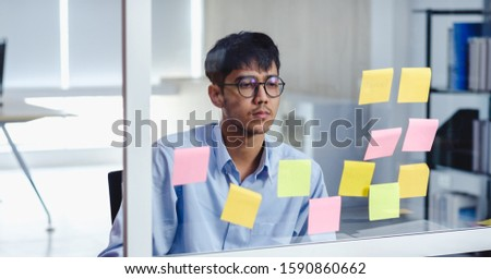 asian businessman looking and writing on sticky note for brainstorming ideas on clear whtieboard at modern office. analyze and synthesis #1590860662