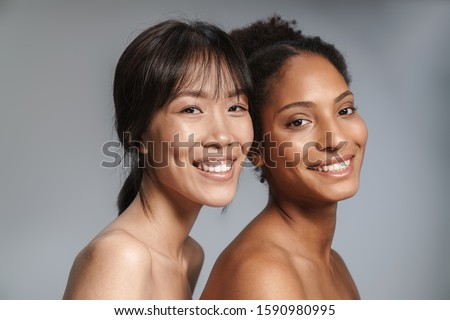 Portrait of two multinational half-naked women posing together and smiling isolated over grey background #1590980995