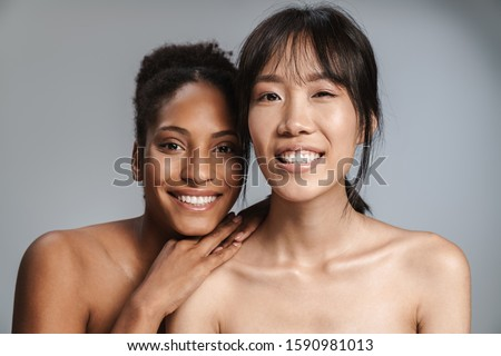 Portrait of two multinational half-naked women smiling and looking at camera isolated over grey background #1590981013