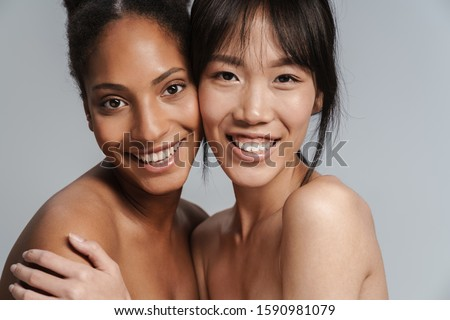 Portrait closeup of two multinational half-naked women hugging and laughing isolated over grey background #1590981079