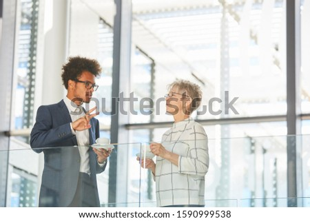 Older business woman talking to young colleague during a coffee break #1590999538