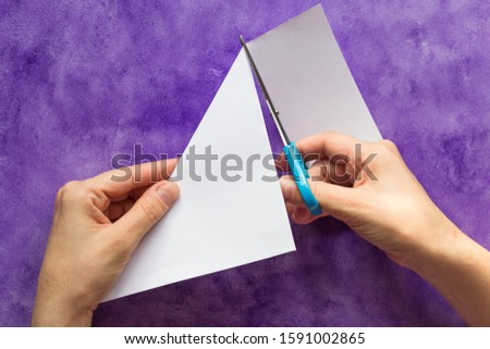 Cutting away edge of sheet of paper with scissors folded corner to make square piece by woman hands on violet surface #1591002865