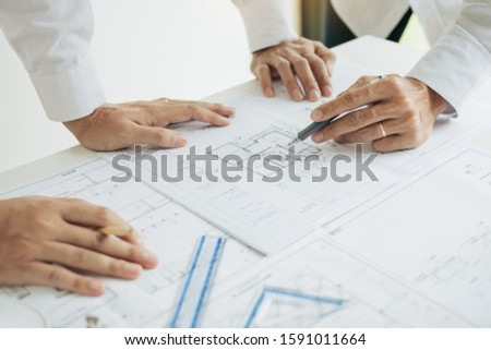 Team architect or engineering people discussion working on table together at a construction site.