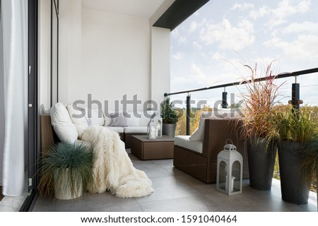 Beautiful decorated balcony with wicker furniture, white pillows and many decorative plants Royalty-Free Stock Photo #1591040464