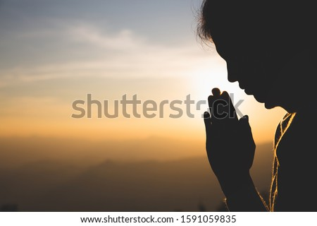 silhouette of a woman  Praying hands with faith in religion and belief in God On the morning sunrise background.  Namaste or Namaskar hands gesture, Pay respect, Prayer position. #1591059835