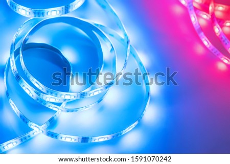 Bright neon LED strip glows blue and red. Copyspace. #1591070242