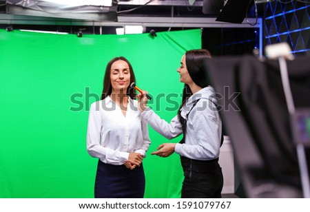 Presenter, makeup artist and video camera operator working in studio. News broadcasting