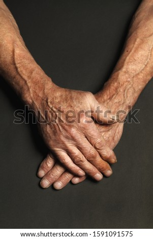 Wrinkled hands of an elderly man on a table close-up isolated on a black background. Top view. #1591091575