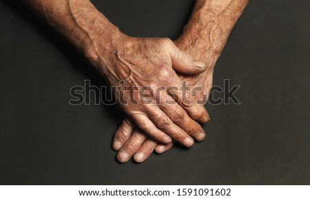 Wrinkled hands of an elderly man on a table close-up isolated on a black background. Top view. #1591091602
