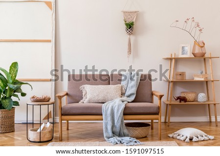 Interior design of living room with brown wooden sofa, macrame, bookstand, coffee table, plants pillows, decoration and elegant accessories. Beige and japandi concept. Stylish home staging. Template.  #1591097515