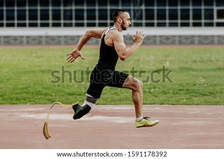 man athlete with prosthetic legs running in track stadium  #1591178392
