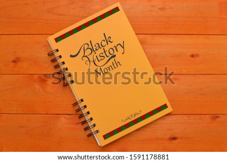 Black History Month book on wood table #1591178881