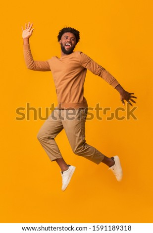 Funny laughing black guy jumping in the air over orange background #1591189318