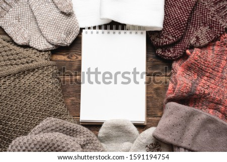 Blank notepad and winter clothes on brown wooden table background. Winter to do list mock up. #1591194754