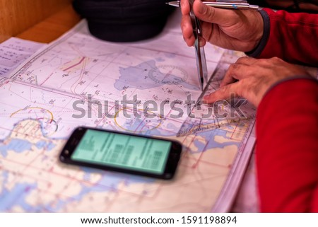 navigation with sea charts in the chart room on a sailing yacht #1591198894