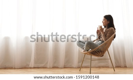 Time to relax. Girl drinking coffee, sitting in wicker chair against window at home, free space #1591200148