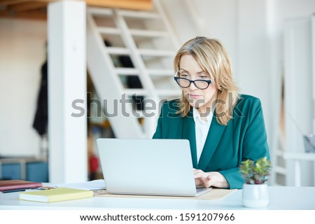 Serious mature manager in eyeglasses sitting at the table and typing on laptop computer she working online #1591207966