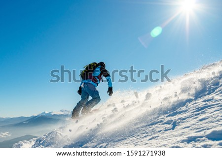 Snowboarder Riding Snowboard in the Mountains at Sunny Day. Snowboarding and Winter Sports #1591271938