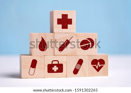 Wooden cubes are icons of icons with honey, analyses, syringe, tablets, pill, band-aid and heart. Close up. #1591302265