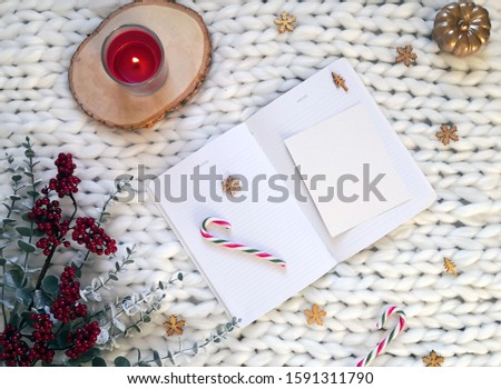 Christmas concept. White notebook with Christmas decorations, candy canes, red candle, wooden snowflakes, red berries branches on white knitted blanket. Winter composition, flatlay, copy space. #1591311790