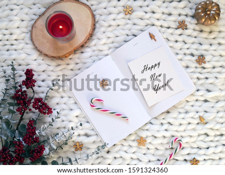 Christmas concept, winter composition. White notebook with Christmas decorations, candy canes, red candle, wooden snowflakes, red berries branches on white knitted blanket. Happy New year text. #1591324360