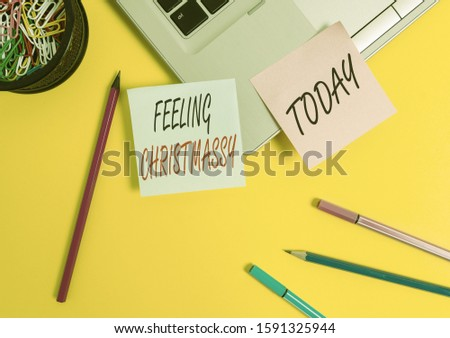 Conceptual hand writing showing Feeling Christmassy. Business photo text Resembling or having feelings of Christmas festivity Laptop sticky notes container pencils markers colored background. #1591325944