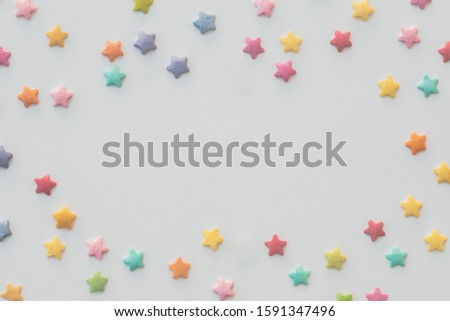 Colorful stars of sprinkles placed as a frame on white background. Room for text or placing an object in the middle. #1591347496