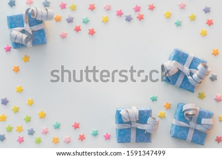 Four blue presents and small stars of sprinkels placed as a frame leaving space in the middle for text or placing an object. #1591347499