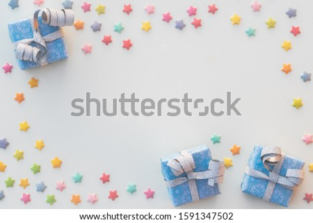 Three blue presents and small stars of sprinkels placed as a frame leaving space in the middle for text og placing an object. #1591347502