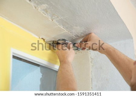 Man plastering window area with putty knife indoors, closeup. Interior repair #1591351411