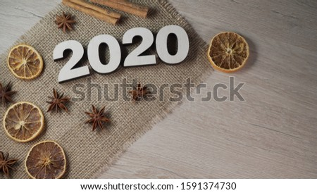 Happy New Year 2020. Symbol from the number 2020 on a textile background. Seasoned with cinnamon and anise. Place for text. View from above. #1591374730