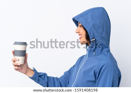 Mixed race woman wearing winter clothes with the hood on and holding a hot takeaway coffee over isolated white background with happy expression #1591408198