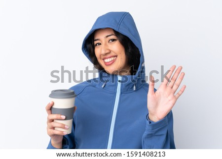 Mixed race woman wearing winter clothes with the hood on and holding a hot takeaway coffee over isolated white background saluting with hand with happy expression #1591408213