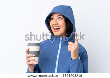 Mixed race woman wearing winter clothes with the hood on and holding a hot takeaway coffee over isolated white background intending to realizes the solution while lifting a finger up #1591408216