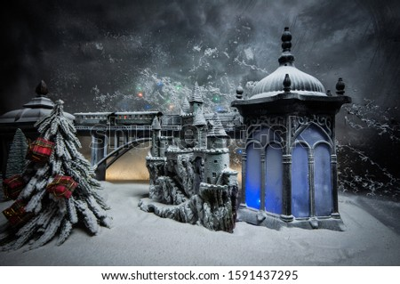 Miniature of winter snowy scene with train on bridge, medieval castle and lantern. Holiday attributes. Night scene. New Year and Christmas concept. Selective focus