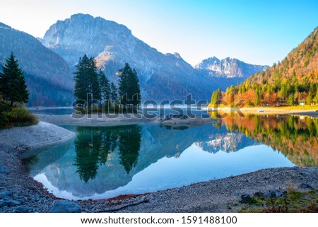 Sunrise and lightbeams on a clear morning at a beautiful mountain lake in north Italy with autumn colored trees on the shore and a stunning reflection of surrounding mountains and island with trees #1591488100
