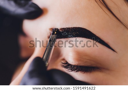 beautician- makeup artist applies paint henna on previously plucked, design, trimmed eyebrows in a beauty salon in the session correction. Professional care for face. #1591491622
