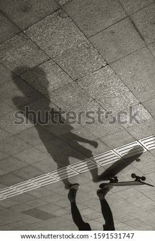 Silhouette of Skateboarder in city. Skateboarder on the sidewalk. the shadow of a skateboarder. Black and white photo #1591531747