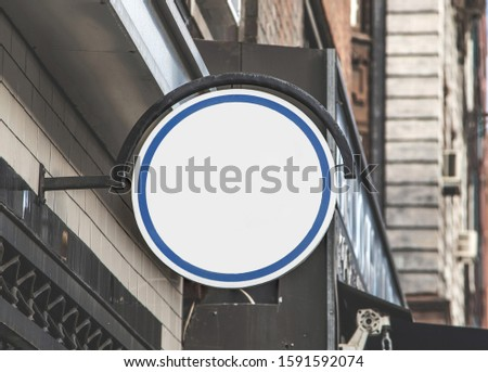 Generic white round mockup sign attached to exterior wall. Insert custom graphics or text. Background for your project.