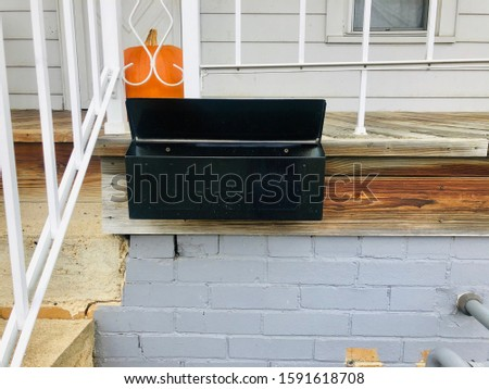 A mailbox is attached to a front porch of a house with a pumpkin behind the box #1591618708