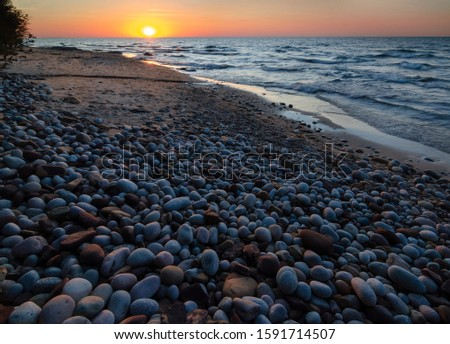 The sun sets over Lake Superior ay the Hurricane River beach in Pictured Rocks National Lakeshore in Alger County, Michigan