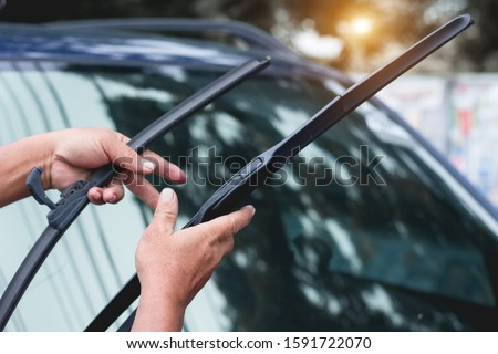 Mechanic replace windshield wipers on car. Replacing wiper bladesChange cars wiper blades. Technician Man changing windshield wipers blades on car. Royalty-Free Stock Photo #1591722070